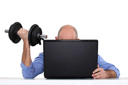 Businessman using weights at his desk photo