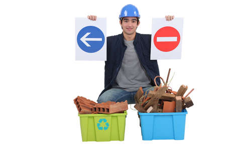 destruct: Worker kneeling by recycle boxes Stock Photo