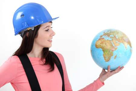 the responsibility: A female construction worker holding a globe