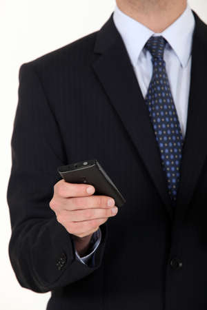 menswear: Close-up of businessman sending text message from mobile