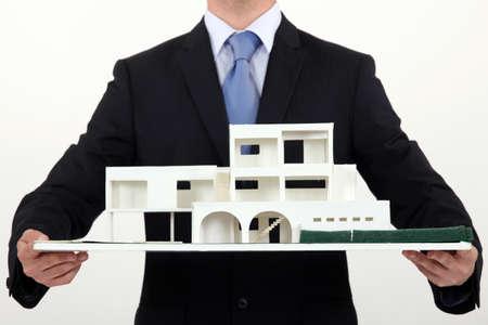 replica: Architect holding scale replica of building