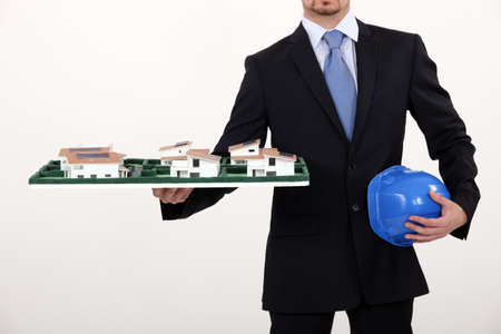 construction plans: Architect with a model housing estate Stock Photo
