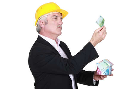 businessman holding a little house made of bills Stock Photo - 15174570