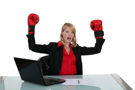 Woman at her desk with boxing gloves photo