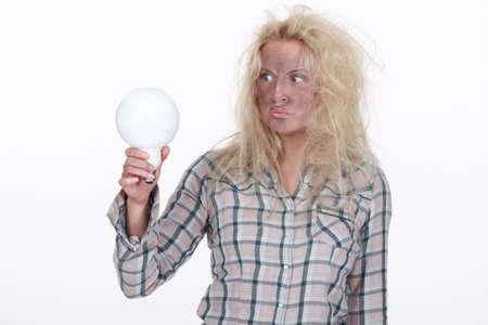 power failure: Shocked blond woman holding light bulb
