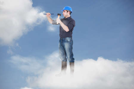 photomontage: Photomontage of a workman driving a nail in the clouds