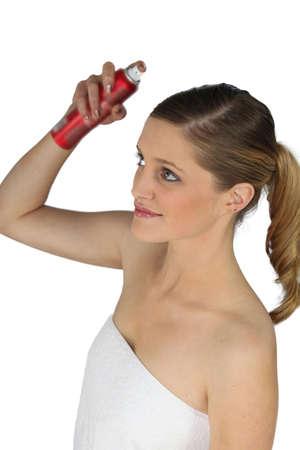 Woman spraying her hair with hairspray photo