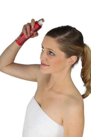 hair conditioner: Woman spraying her hair with hairspray
