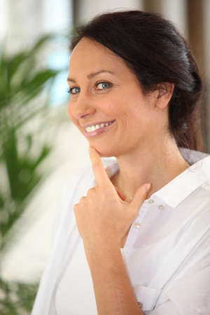 blue eyed: brunette with finger on chin Stock Photo