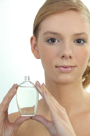 perfume woman: Young woman holding a bottle of perfume Stock Photo