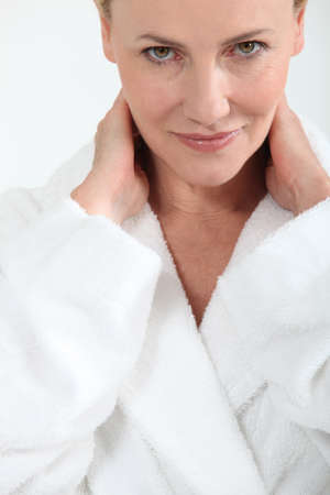 Woman in bath robe with hands behind neck Stock Photo - 15175180