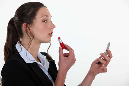 conceited: Woman applying lipstick