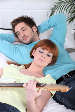 pegheads: Woman playing the guitar for her boyfriend