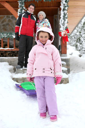 sledging people: couple posing with daughter near chalet at ski resort