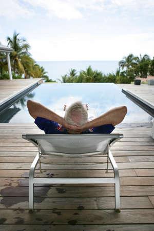 Senior man relaxing poolside photo
