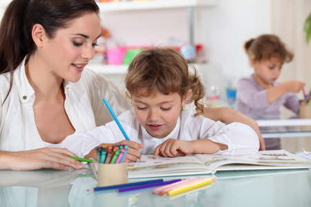 Woman and child colouring at a desk Stock Photo