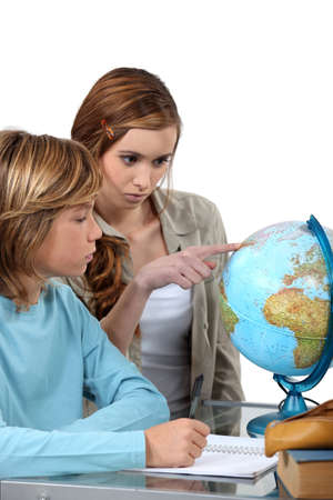 Boy and girl looking at a globe photo