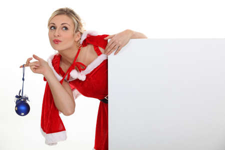 mrs claus: Woman dressed as Mrs  Claus and holding a blank board