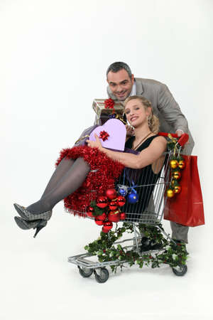 christmas budget: Couple with trolley full of Christmas gifts Stock Photo
