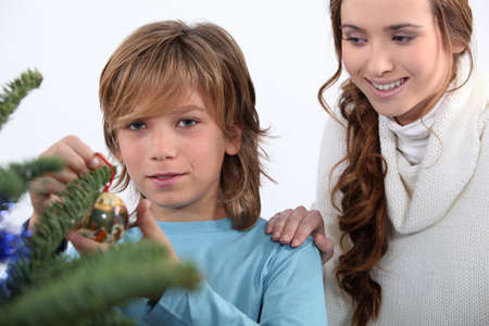 child decorating Christmas tree photo