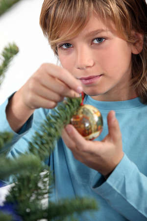 A kid decorating a Christmas tree  photo
