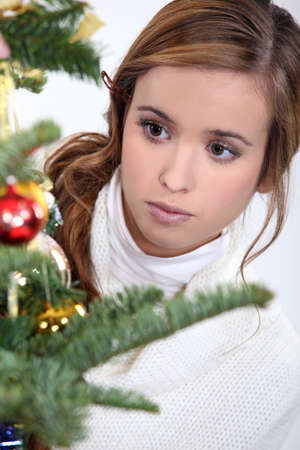 poker faced: Young woman looking at Christmas ornaments Stock Photo
