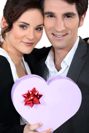 Romantic couple with heart-shaped box photo