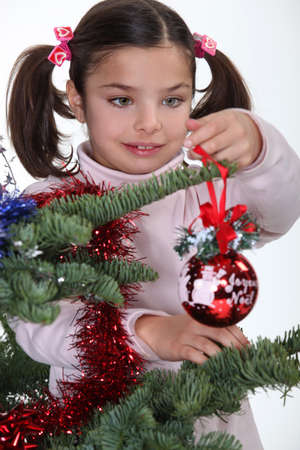 fake christmas tree: Young girl decorating a Christmas tree
