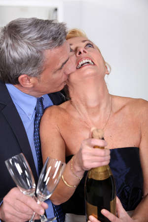 popping cork: Couple popping a champagne cork Stock Photo