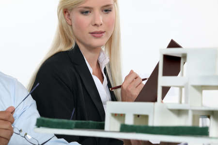 property management: Architect and co-worker looking at model building Stock Photo