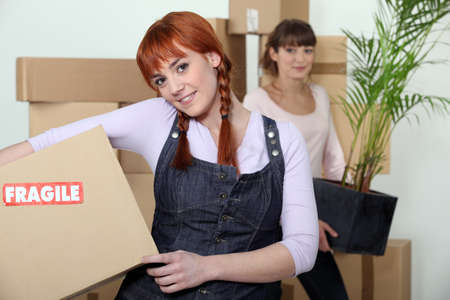 settling: Young women on moving day Stock Photo