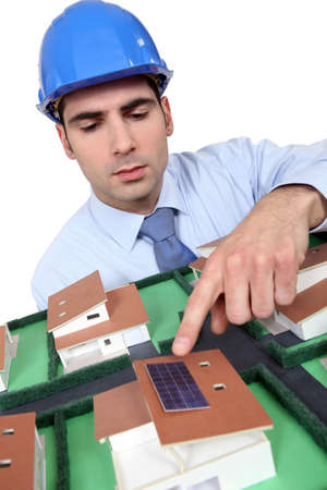 Architect pointing to solar panel on model house photo