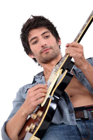 bare chested: young man playing electrical guitar, his shirt is open, the photo is taken from below Stock Photo