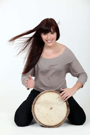 bongo drum: Brunette playing a bongo drum