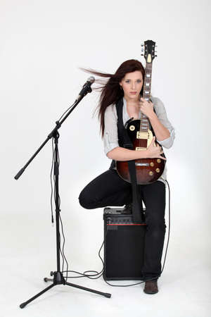 Musician hugging her guitar and posing with her equipment photo