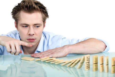 poker faced: Man playing with dominoes
