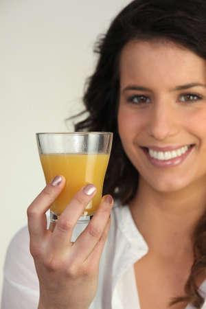 elated: Woman holding orange juice Stock Photo