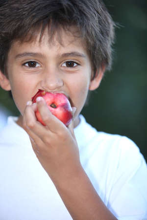 Young boy eating a nectarine Stock Photo - 15223770