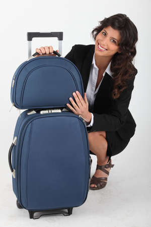 Woman quatting with suitcase photo