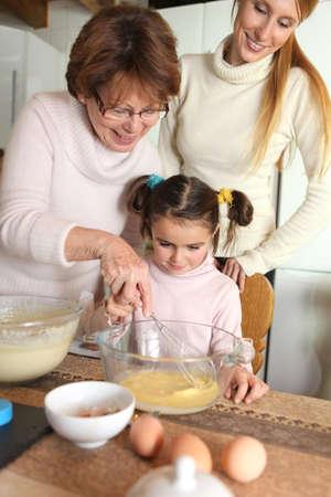 generosity: abuela haciendo crepes con nietecita Foto de archivo