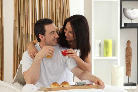 reggeli: boldog pár reggelizik az ágyban Stock fotó