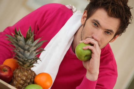 Pensive young man eating fruit photo