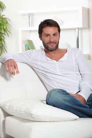 loosen up: Man sat on sofa Stock Photo