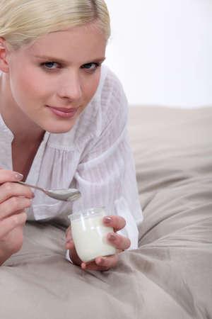Woman eating yoghurt photo