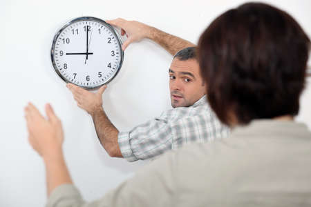 Couple straightening a crooked clock Stock Photo - 15496713
