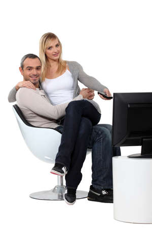 Couple sitting in a chair watching television photo