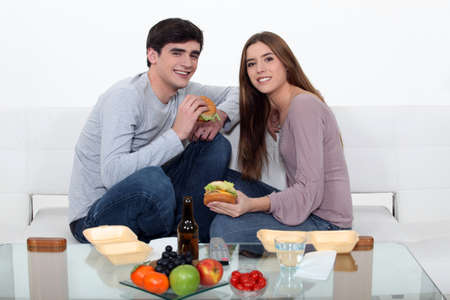 eating fast food: Couple eating fast food in the couch Stock Photo