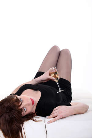 drunk young woman lying in sofa with flute of champagne Stock Photo - 15224264