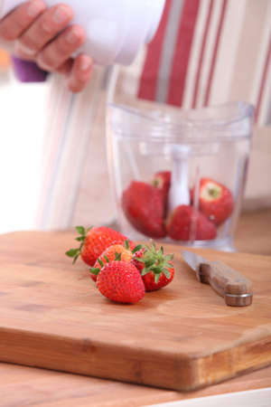 Woman putting strawberries in a blender photo