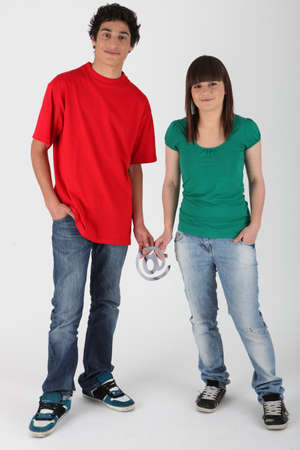 web presence internet presence: Teenage couple holding an @ sign Stock Photo